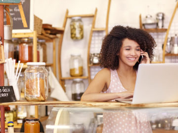 Smiling coffee shop owner researches entrepreneur business loans