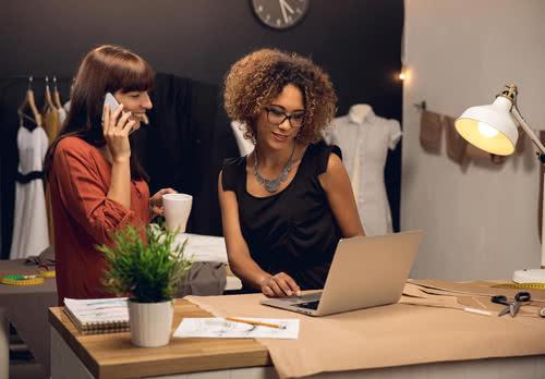Two women research C corporation vs S corporation status on laptop