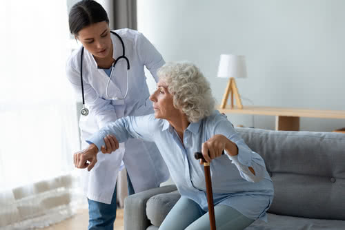 Attentive female nurse give help disabled senior woman with walking stick stand up from couch at home, caring young caregiver or doctor assist sick old lady with cane, elderly healthcare concept
