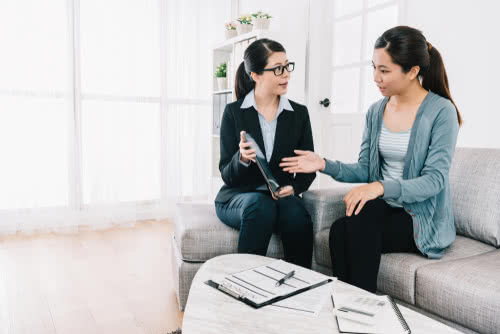 housewife asking the questions about the insurance plan on the tablet to the businesswoman. accountant doing contract work in home office. meeting at home concept.