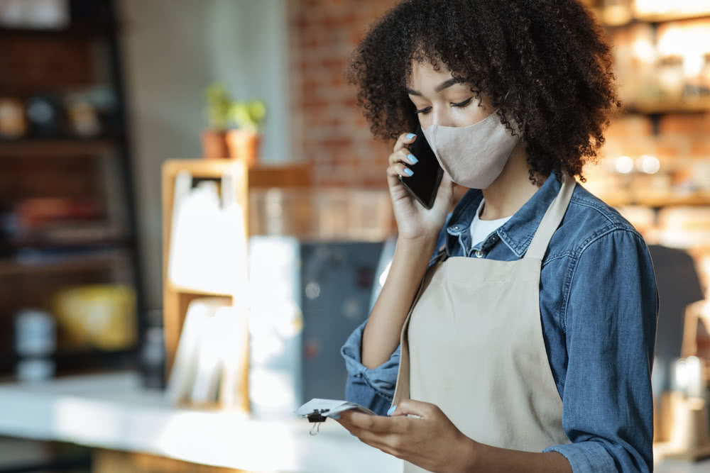 A Black small business owner calculates her annual revenue.